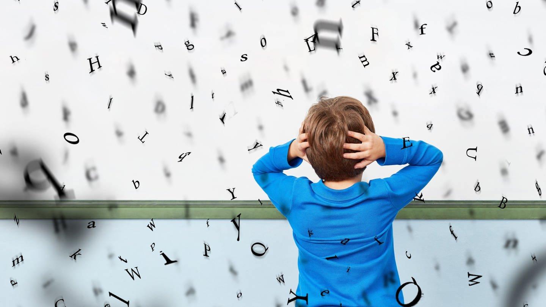 Kind vor einer Tafel mit fliegenden Buchstaben: Die Ursache für Legasthenie bzw. LRS ist meist genetisch. Sie ist nicht heilbar; eine spezielle Lerntherapie kann die Schwierigkeiten aber mindern. (Foto: picture-alliance / Reportdienste, picture alliance/Zoonar)