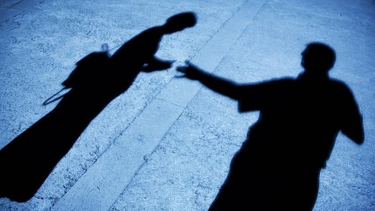 Ein Männerschatten greift nach dem Schatten einer Frau mit Rucksack