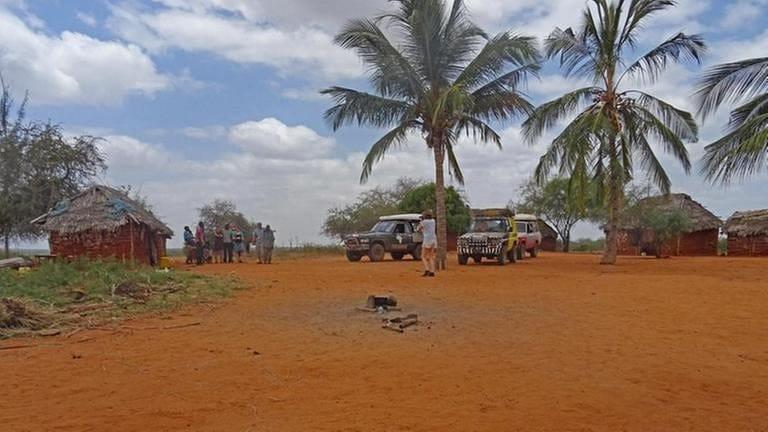 Pickups und Personen auf einem Dorfplatz in Afrika