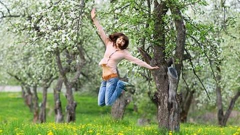 Junge Frau springt auf einer blühenden Frühlingswiese in die Höhe. (Foto: Colourbox, Model Foto: Colourbox.de -)