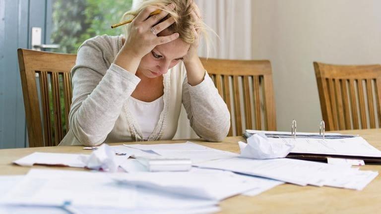 Frau sitzt vor einem riesigen Haufen ungeordneten Papiere und stützt den Kopf auf ihre Hände. (Foto: Getty Images, Thinkstock -)