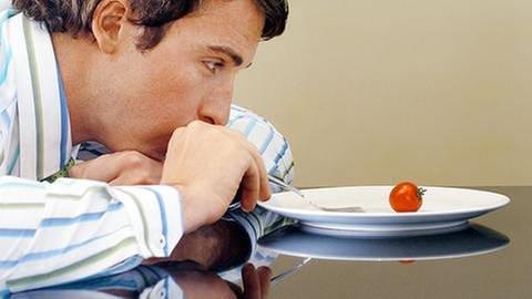 Mann sitzt über einen Teller gebeugt und stochert mit seiner Gabel auf einem Teller mit nur einer kleinen Cocktail-Tomate herum. (Foto: Getty Images, Thinkstock -)