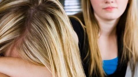 Zwei Mädchen sitzen in einem Unterrichtsraum.