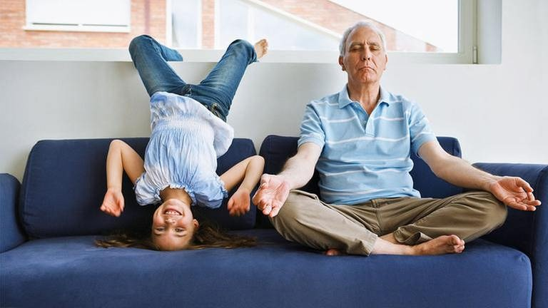 Großvater sitzt auf einem Sofa im Schneidersitz und meditiert. Neben ihm albert ein kleineres Mädchen herum und lacht. (Foto: Getty Images, Thinkstock -)