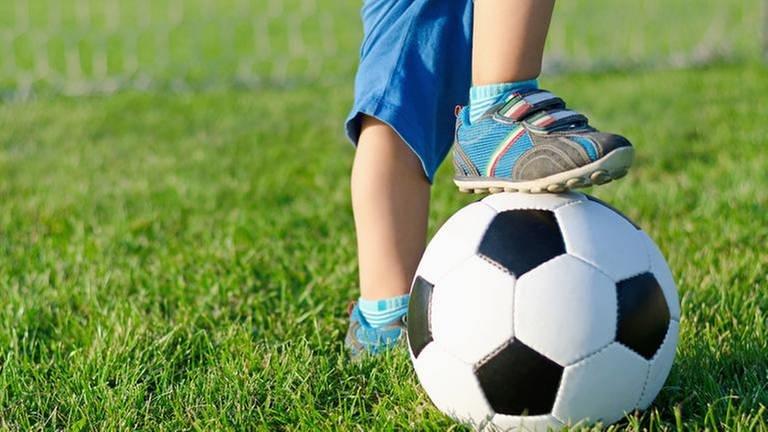 Ein kleiner Junge stützt sich während des Fußballspiels mit einem Fuß auf dem Ball ab.