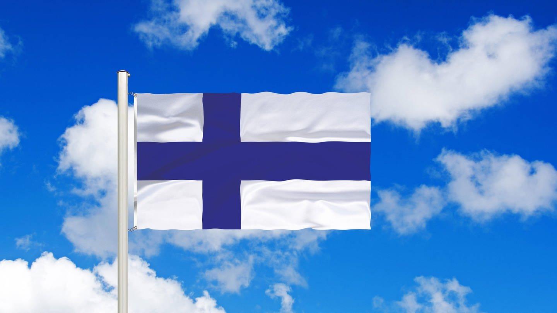 Flagge von Finnland vor blauem Himmel mit weißen Wolken (Foto: Imago, imago images / blickwinkel)