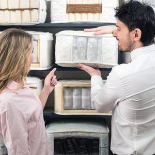 Eine Frau lässt sich in einem Matratzen-Geschäft von einem Verkäufer beraten. (Foto: Getty Images, Thinkstock -)