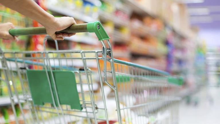Eine Frau schiebt einen Einkaufswagen durch den Supermarkt