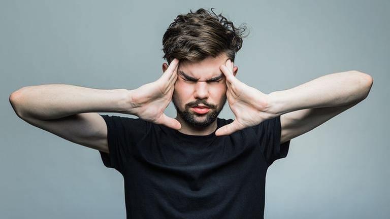 Ein junger Mann drückt seine Finger an die Schläfen und verzieht sein Gesicht zu einer Grimasse. (Foto: Colourbox, Model Foto: Colourbox.de -)