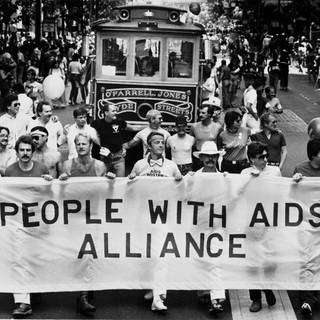 "Demonstranten tragen während der 13. jährlichen Gay Freedom Day Parade am 27. Juni 1983 in San Francisco ein Banner mit der Aufschrift ""People With Aids Alliance"" (Foto: picture-alliance / Reportdienste, picture alliance / AP Images)"
