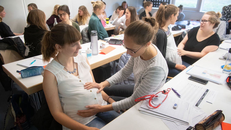 Seit dem Wintersemester 2018/2019 kann an der Universität Tübingen Hebammenwissenschaft studiert werden. Im Bild: Zwei Studentinnen üben eine Betreuungssituation (Foto: dpa Bildfunk, picture alliance/dpa | Marijan Murat)