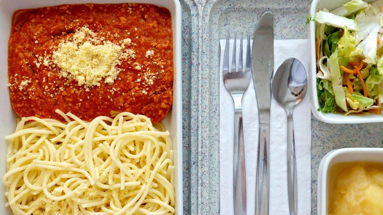 Essenstablett mit Spaghetti, Salat und Kompott: Gemüse, das stundenlang warmgehalten wird, zerkochte Nudeln, fades Fleisch oder klebriger Brei: In Pflegeheimen und Krankenhäusern verstößt das Speisenangebot mitunter gegen die Menschenwürde.