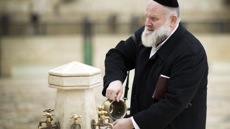 Ein jüdischer Mann wäscht sich vor dem Gebet an der Klagemauer in der Altstadt von Jerusalem die Hände