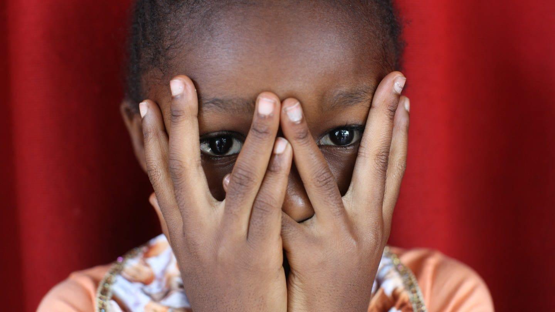 Afrikanisches Mädchen hält sich die Hände vors Gesicht: Sexualisierte Gewalt bleibt eine Kriegswaffe. Überlebende Frauen in Bosnien oder Ruanda leiden bis heute unter Ausgrenzung – so wie die Kinder aus den Vergewaltigungen.