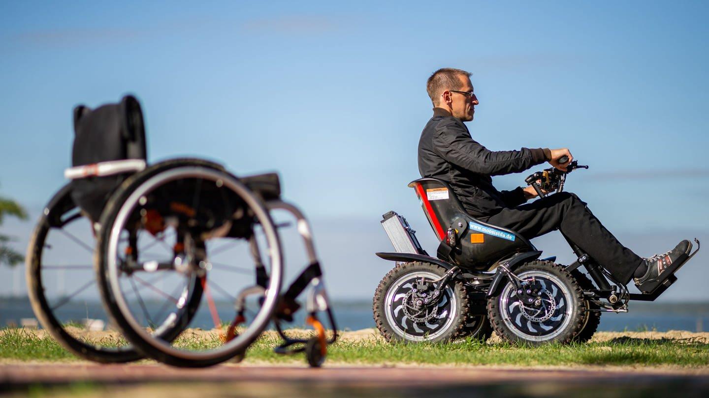 Mann fährt in einem geländegängigen Rollstuhl, daneben steht sein Alltagsrollstuhl: Raffinierte Technik eröffnet Behinderten neue Möglichkeiten der Mobilität. Der Funsport befeuert die Entwicklung. (Foto: dpa Bildfunk, picture alliance/dpa | Mohssen Assanimoghaddam)