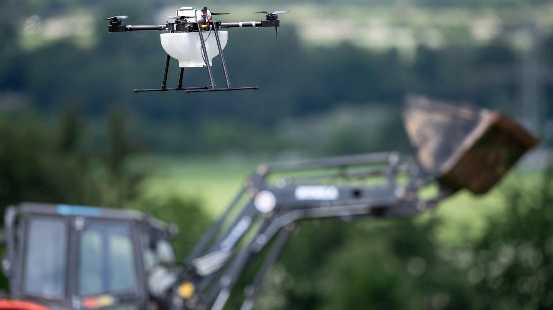 Eine Drohne fliegt vor einem Traktor über einem Getreidefeld. Mit
