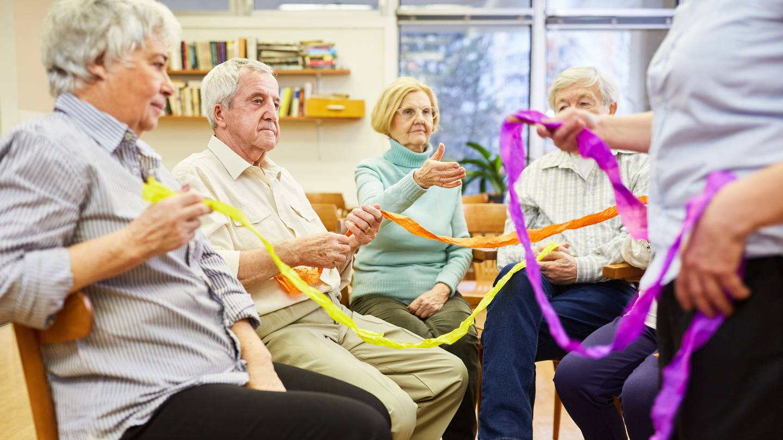 Senioren mit Demenz machen eine Übung mit bunten Stoffbändern für Interaktion