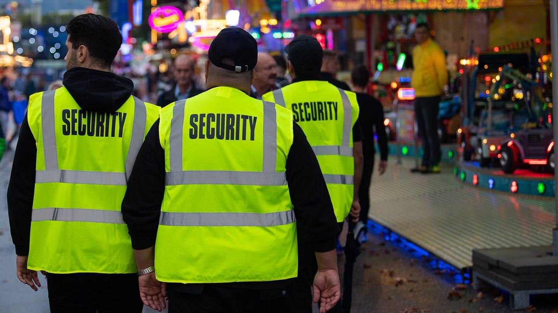Mitarbeiter eines privaten Sicherheitsdiensts gehen zu Beginn des 174. Cannstatter Volksfests über das Gelände (Foto: picture-alliance / Reportdienste, picture alliance/dpa   Sebastian Gollnow)