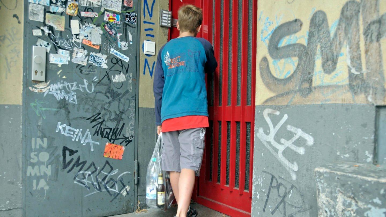 Ein Junge in einem heruntergekommenen Hauseingang; in der Hand eine Tüte mit Pfandflaschen: Jedes fünfte Kind in Deutschland wächst in Armut auf.