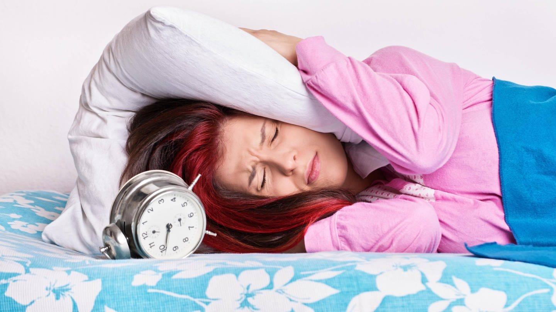 Frau hält sich Kissen aufs Ohr, um den Wecker nicht zu hören: Jeder sollte so lange schlafen, bis er ausgeschlafen ist. Wer zu lange im Bett bleibt oder zu kurz schläft, kann Schlafstörungen entwickeln.