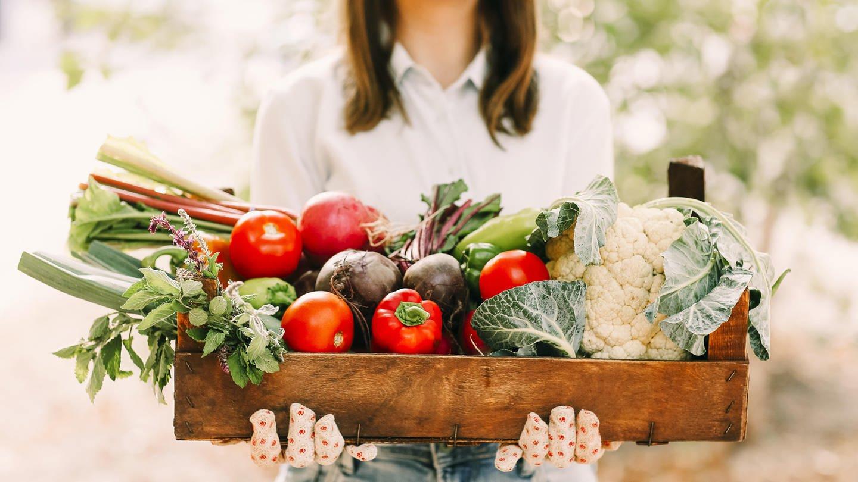Eine Frau trägt eine Kiste voll Gemüse: Immer mehr Menschen legen selbst Hand an und arbeiten bei Landwirten mit