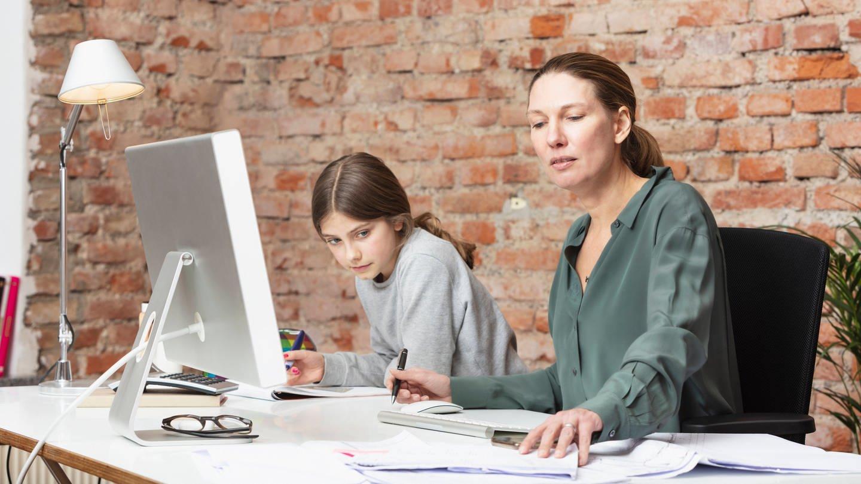 Mutter arbeitet im Homeoffice am Laptop, Tochter macht daneben Hausaufgaben: Eltern leisten