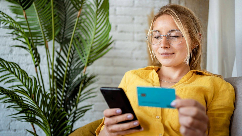 Eine Frau bezahlt online mit Smartphone und Kreditkarte