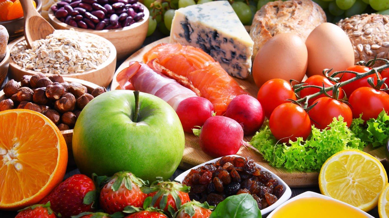 Reich gedeckter Tisch mit Obst, Gemüse, Nüssen, Eiern, Käse, Getreideprodukten: