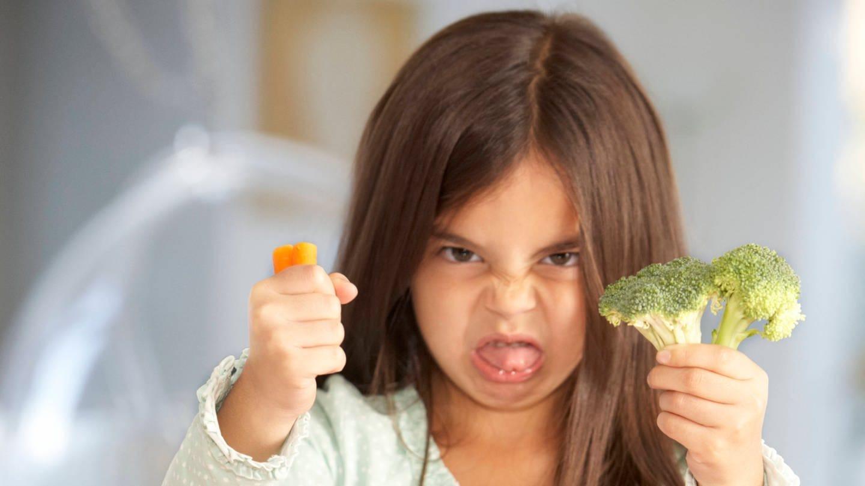 Kleines Mädchen schneidet wilde Grimasse und hält Brokkoli und Möhre von sich: Wie etwas schmeckt, legen nicht nur Zunge und Nase fest. Auch unsere Erfahrungen bestimmen darüber, vor allem aber die Kultur, in der wir leben.