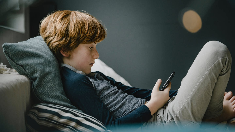 Ein Junge liest auf einem Smartphone (Foto: Imago, imago images/Westend61)