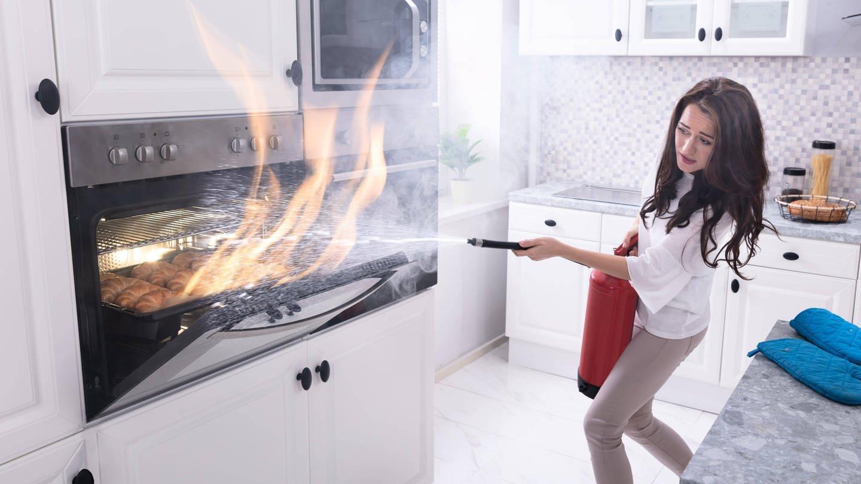 Eine Frau versucht, mit einem Feuerlöscher einen brennenden Backofen zu löschen (Foto: Imago, imago images / Panthermedia)