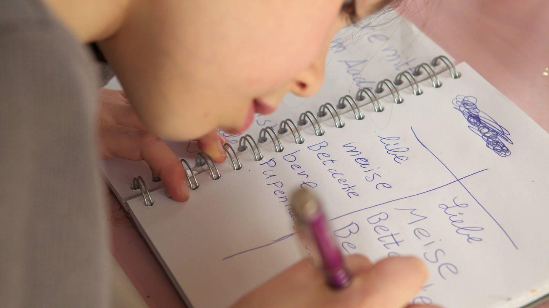 Eine Grundschülerin schreibt Wörter in ein Heft (Foto: Imago, JOKER)