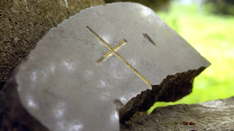 Kaputter Grabstein mit einem Kreuz (Foto: Imago, imago)