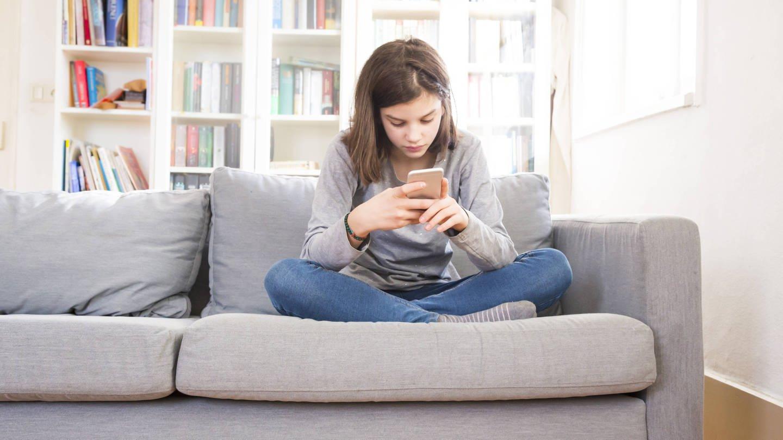 Mädchen sitzt mit Smartphone auf der Couch (Foto: Imago, imago/Westend61)