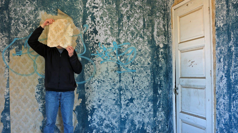 Psychologie. Ein Mann hält sich in einem blauen Raum ein Stück Tapete vors Gesicht (Foto: Colourbox)