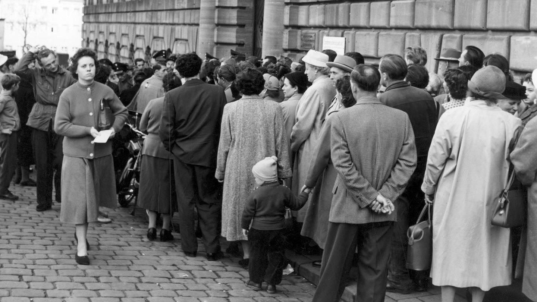 Menschen stehen am 18.10.1957 vor der Ortskrankenkasse in Nürnberg Schlange. Der Andrang war so groß, dass die Nürnberger Stadtpolizei zur Hilfeleistung herangezogen wurde. (Foto: picture-alliance / Reportdienste, Karl Schnörrer/(c) dpa - Report)