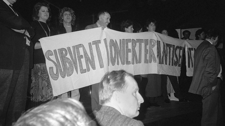 Demonstranten, unter ihnen Ignatz Bubis (Mitte), besetzen am 31.10.1985 die Bühne des Frankfurter Kammerspiels und entrollten ein Transparent mit der Aufschrift
