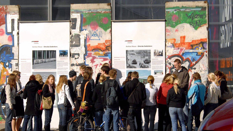 imago/PEMAX (Foto: Imago, Schüler während einer Geschichtsstunde vor Resten der Berliner Mauer und Informationstafeln am Potsdamer Platz in Berlin (2007))