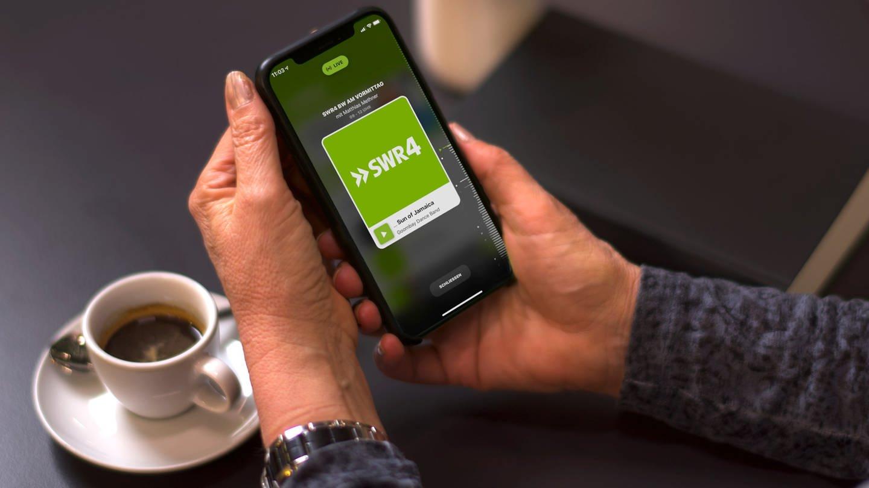 Eine Hand hält ein Smartphone, auf dem die SWR4 App geöffnet ist