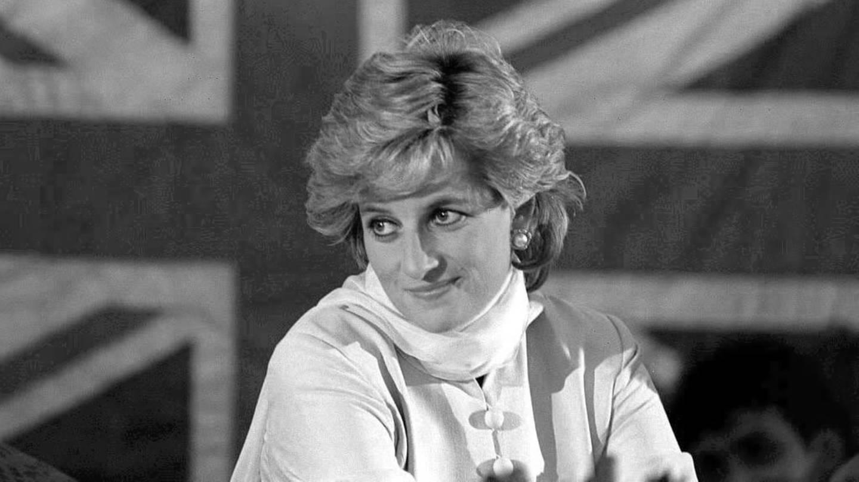 Schwarz-weiß Aufnahme von Lady Diana, die vor einer großen Flagge von England sitzt.