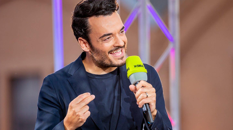 Schlagersänger Giovanni Zarrella singt bei einem Konzert in ein Mikrofon