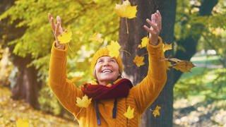 Eine Frau wirft Herbstlaub in die Luft (Foto: Imago, Panthermedia)