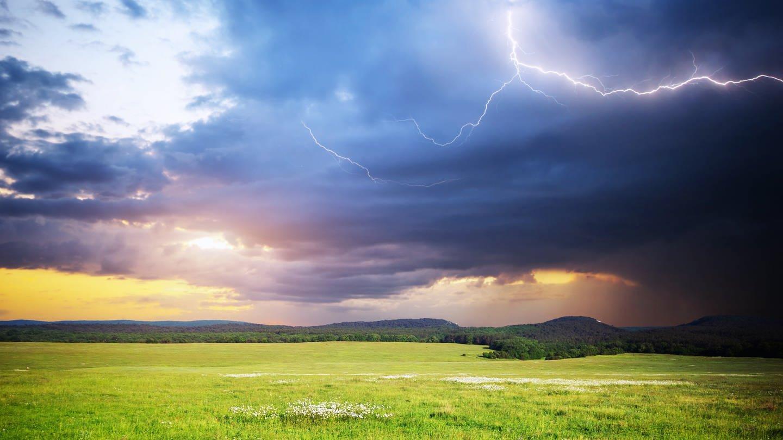 Sonne und Gewitterwolken über Feldern und Hügeln