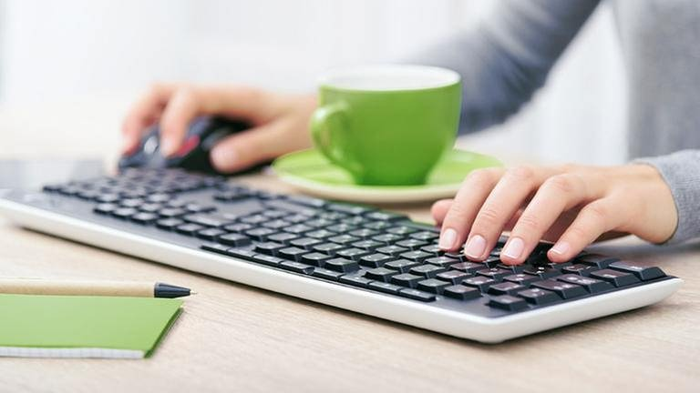 Eine Frau sitzt vor ihrem Computer und einer grünen Tasse und tippt in ihre Tastatur (Foto: Colourbox)