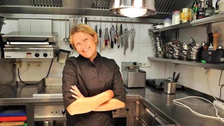Köchin Eva Eppard in schwarzer Kochjacke steht in ihrer Restaurantküche (Foto: SWR, Axel Mengewein -)