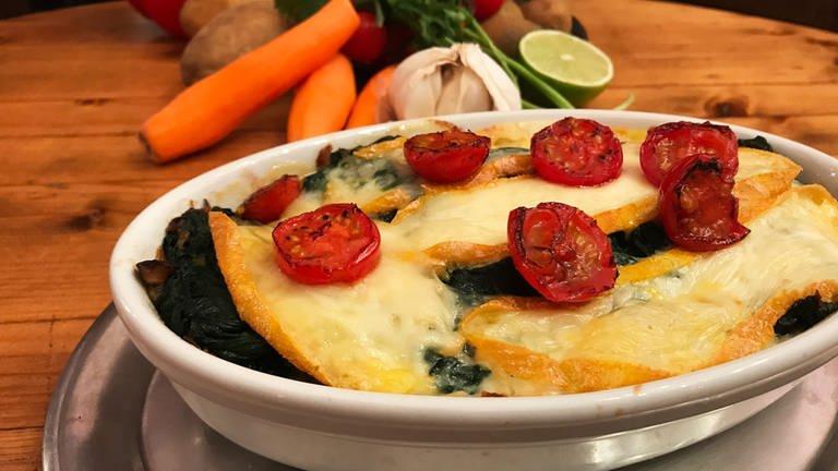 weiße Auflaufform mit Kartoffel-Spinat-Käseauflauf mit halbierten, kleinen Tomaten als Deko (Foto: SWR, SWR)