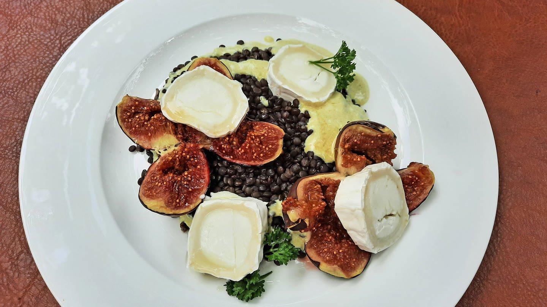 weißer Teller mit einem Salat aus schwarzen Linsen, Feigen und Ziegenkäse