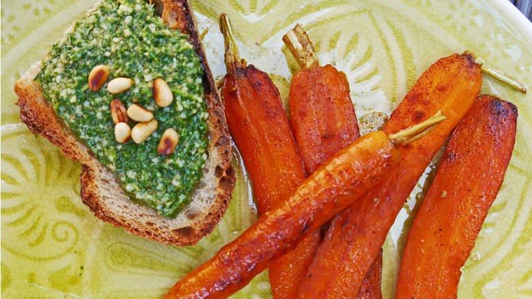 Gebratene Möhren am Stück mit einer Scheibe Brot mit Möhrenpesto auf grünem Teller. (Foto: SWR, SWR4 Rheinland-Pfalz)