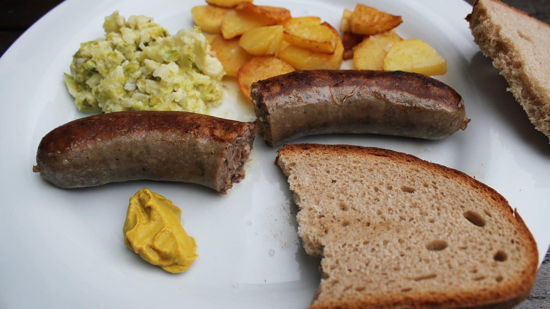 weißer Teller mit einer Wildschwein-Bratwurst durchgeschnitten, dazu eine halbe Scheibe Brot und Senf, Bratkartoffeln und etwas Salat
