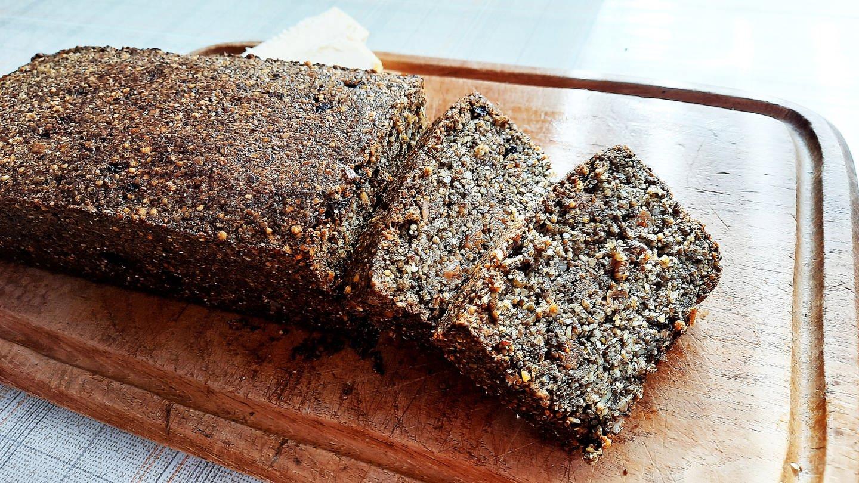 dunkles Körner-Hanf-Brot, angeschnitten, auf einem Holzbrett